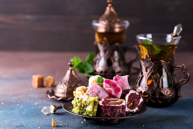 Doces turcos tradicionais com menta de chá em um copo tradicional o