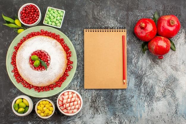 Doces, um bolo apetitoso, doces coloridos, limas, caderno, lápis, romãs