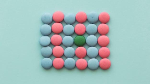 Doces verdes dispostos nos doces-de-rosa e azuis em fundo colorido