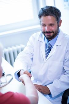 Doctor agitando as mãos com o paciente no consultório médico
