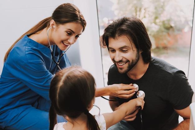 Doctor and kid play ouça o homem pelo estetoscópio