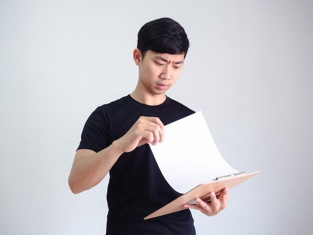 Documento aberto de jovem asiático em rosto sério de prancheta de madeira em branco isolado, conceito de trabalhador