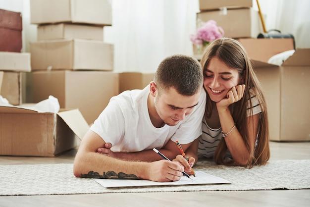 Documento de arquivamento. casal jovem alegre em seu novo apartamento. concepção de movimento.