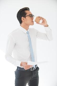 Documento de beber e segurar do homem de negócios asiático