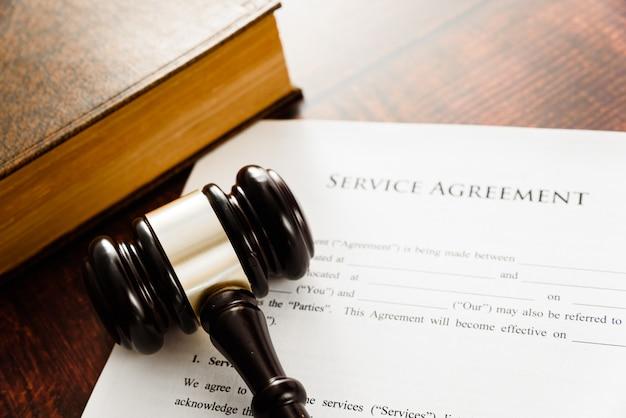 Documento de contrato de serviço, livro e martelo