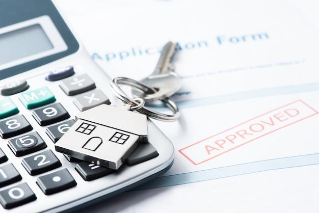 Documento de empréstimo aprovado para hipoteca com chaves da casa