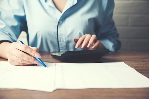 Documento de mão de mulher de negócios e calculadora na mesa de escritório