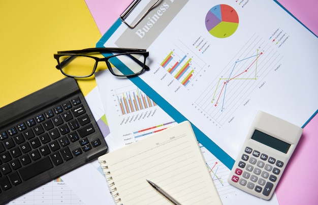 Documento de papel de relatório gráfico financeiro e empresarial gráfico com papel de caderno aberto de calculadora