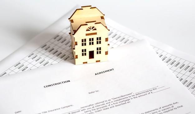 Documento em papel de contrato de contrato com casa de madeira, compra e venda de imóveis ou ideia de conceito de hipoteca de investimento de propriedade para o futuro.