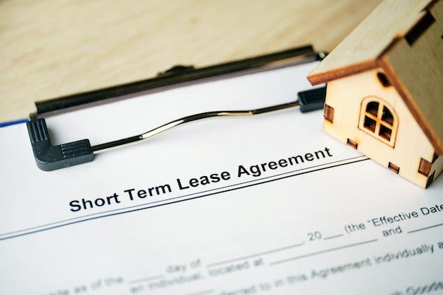 Documento jurídico contrato de locação de curto prazo em papel com caneta.