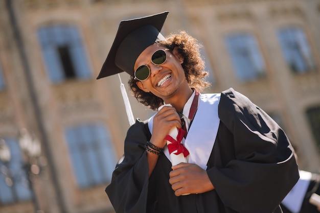 Documento precioso. rapaz alegre usando boné de mestre e óculos escuros, abraçando seu diploma no pátio da universidade.