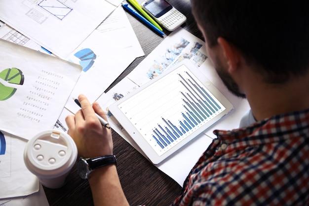 Documentos comerciais na mesa do escritório com tablet digital e diagrama comercial gráfico e homem trabalhando