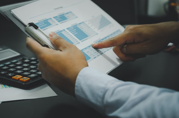 Documentos comerciais nas mãos de um homem de negócios e uma calculadora em sua mesa.