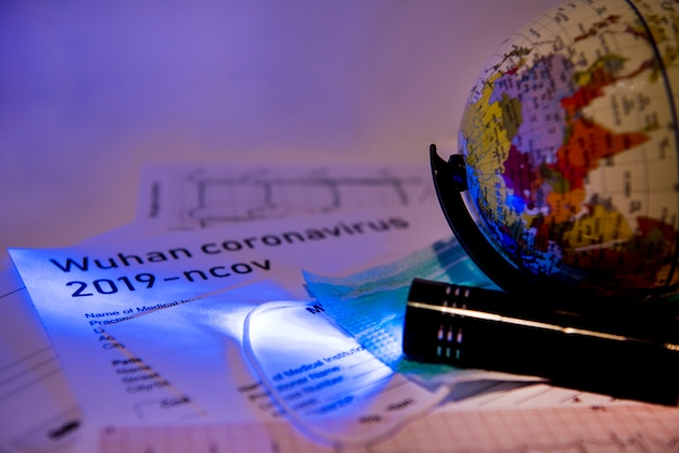 Documentos de medicina sob luz ultravioleta com um pequeno globo nele