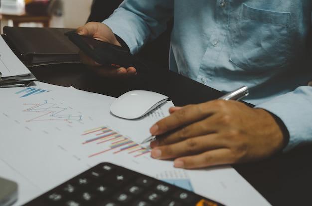 Documentos de negócios, gráficos e relatórios de marketing e vendas. o crescimento do negócio. empresários segurando telefones celulares.