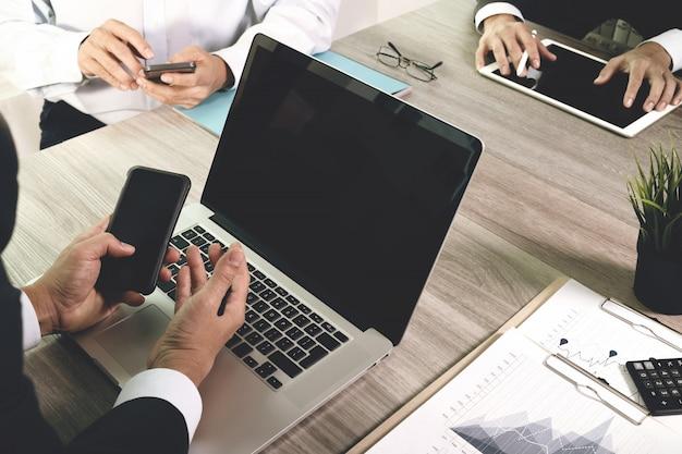 Documentos de negócios na mesa de escritório com telefone inteligente e computador portátil de tela em branco