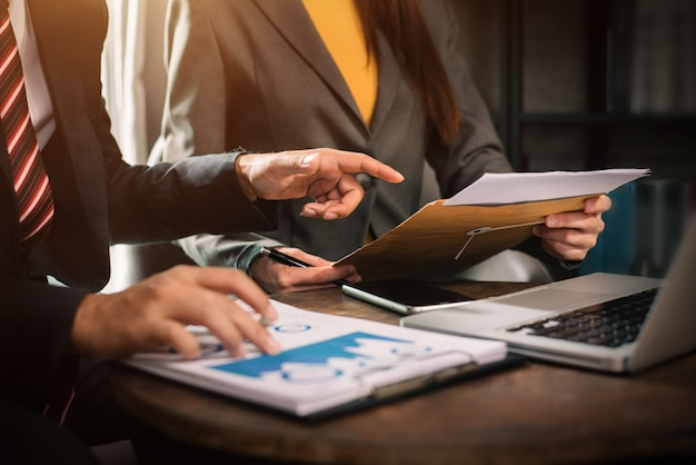 Documentos de negócios na mesa do escritório com smartphone, tablet e laptop e gráfico com diagrama de rede social e dois colegas discutindo dados no escritório.