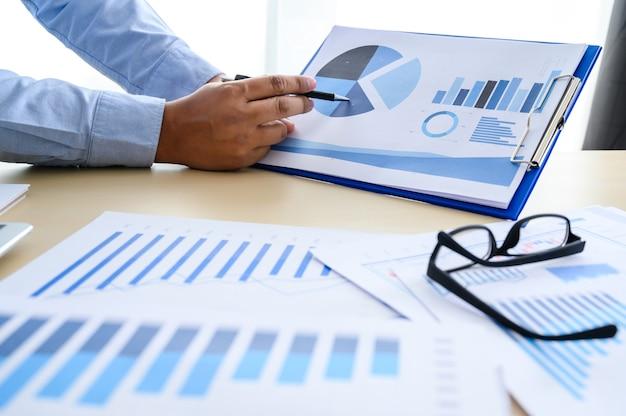 Documentos de negócios no escritório gráfico financeiro com diagrama de rede social discutindo dados de análise de dados as tabelas e gráficos