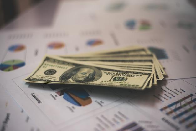 Documentos de negócios no local de trabalho com dinheiro de usd dólar no fundo.