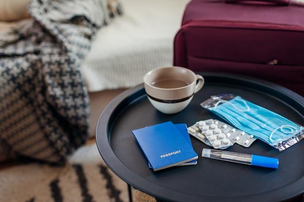 Documentos de passaporte, bagagem e comprimidos com máscara médica para viajar