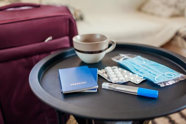Documentos de passaporte, bagagem e comprimidos com máscara para viajar