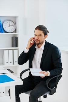 Documentos de trabalho de escritório de homem com tecnologia de telefone na mão