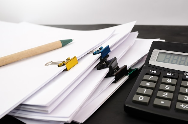 Documentos do office, pastas, papéis com calculadora e caneta na mesa.