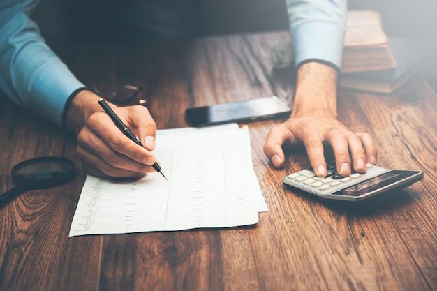 Documentos e calculadora de mão de homem