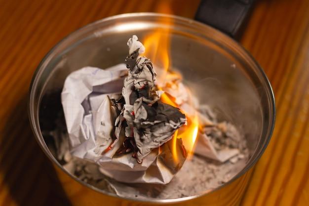 Documentos em chamas em uma pequena panela de prata documentos oficiais, destruição de memórias, conceitos rituais