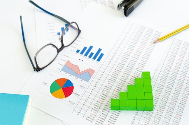 Documentos financeiros, com cubos verdes dispostos em um gráfico de colunas como um conceito de crescimento, ganho ou receita