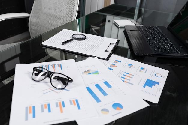 Documentos financeiros com lupa e seguro estão na mesa preta em close-up do escritório