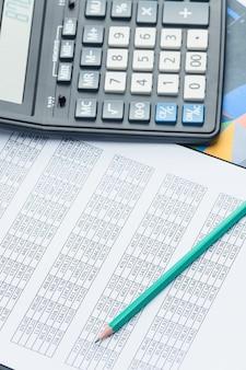 Documentos financeiros de negócios, calculadora de escritório e caneta em cima da mesa. números e gráficos. mesa preta