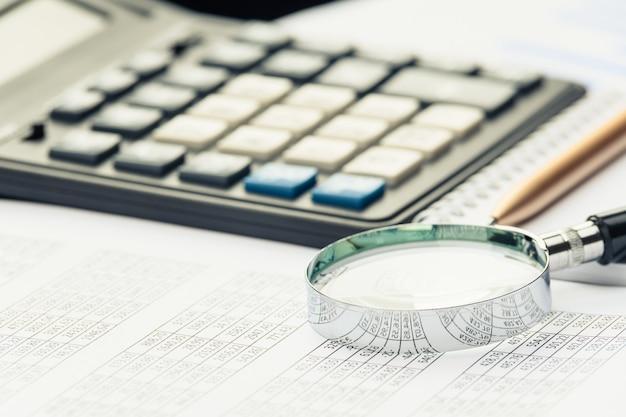 Documentos financeiros de negócios, calculadora de escritório e caneta em cima da mesa. números e gráficos