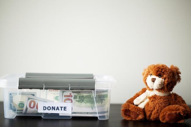 Doe caixa com dólares e um ursinho de pelúcia