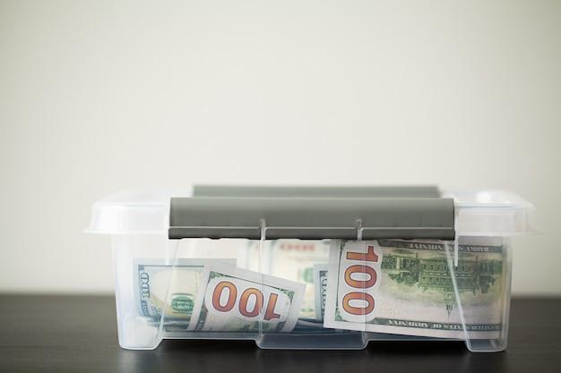 Doe caixa com dólares na mesa de madeira
