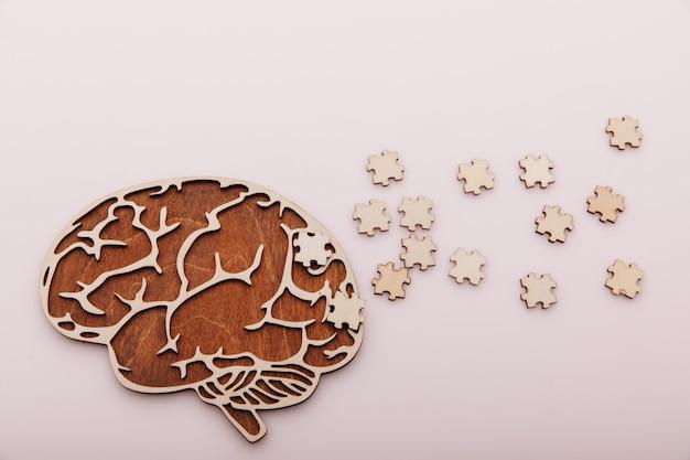 Doença de alzheimer e conceito de saúde mental cérebro e quebra-cabeça de madeira em um fundo rosa