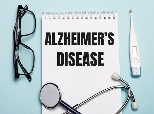 Doença de alzheimers escrita em um bloco de notas branco ao lado de um estetoscópio, óculos de proteção e um termômetro eletrônico em uma parede azul clara. conceito médico.