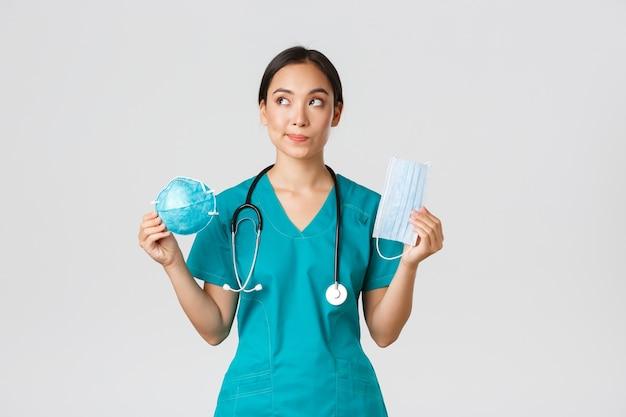 , doença de coronavírus, conceito de trabalhadores de saúde. médica asiática sorridente pensativa, médico de jaleco procurando um sonho no canto superior esquerdo, segurando o respirador e a máscara médica.