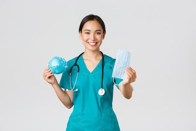 , doença de coronavírus, conceito de trabalhadores de saúde. médica simpática, médica asiática em uniforme mostrando respirador e máscara médica, fornece equipamento de proteção individual para a equipe