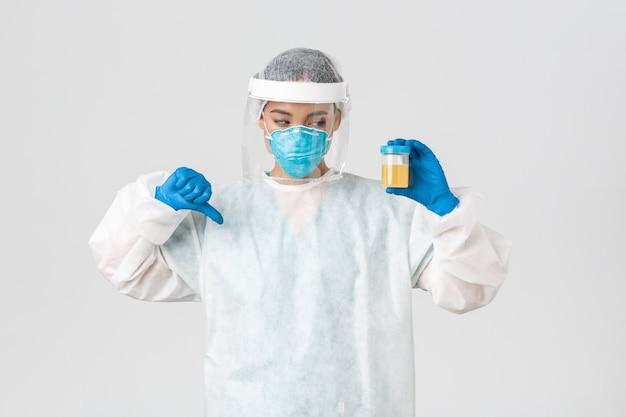 , doença de coronavírus, conceito de trabalhadores de saúde. vista lateral de um funcionário sério do laboratório de tecnologia, pesquisador em equipamentos de proteção individual mostrando o polegar para baixo em desaprovação, resultado de análise ruim