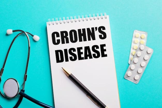 Doença de crohn escrita em um bloco de notas branco perto de um estetoscópio, canetas e comprimidos em um fundo azul claro