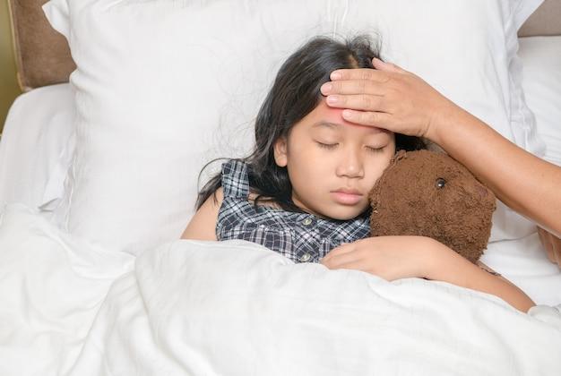 Doença de uma linda garota asiática e a mão da mãe tocam sua testa para verificar a temperatura, os cuidados de saúde e o conceito de amor