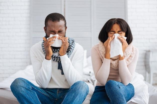 Doença desagradável. jovem casal agradável sentado na cama e espirrando enquanto está doente
