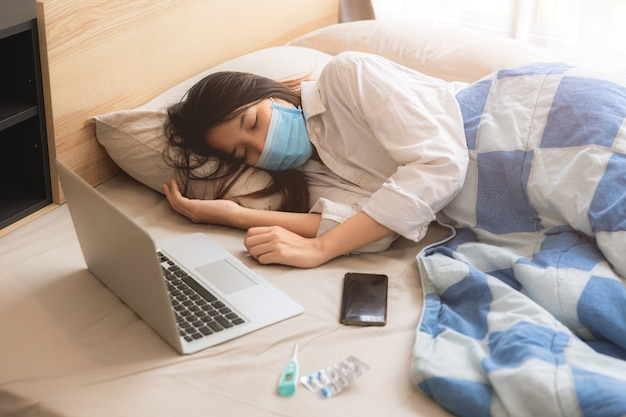 Doença doente adolescente de menina asiática deitada na cama usando máscara facial com computador portátil.