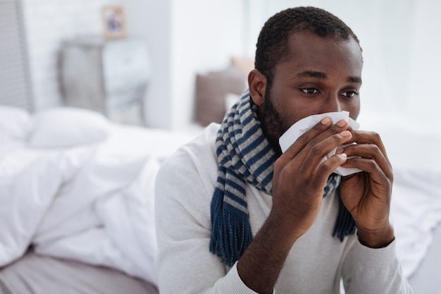 Doença exaustiva. homem triste e exausto ficando em casa sentado na cama com um lenço nas mãos