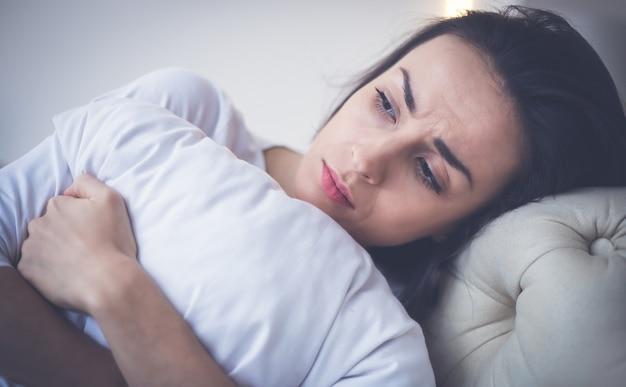 Doença. foto de close-up de uma menina doente, que está deitada em sua cama e abraçando um travesseiro.