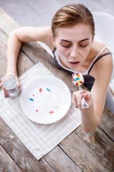 Doença grave. mulher pálida e triste tomando uma colher de comprimidos enquanto estava gravemente doente