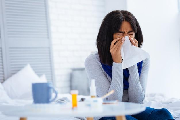 Doença insuportável. mulher jovem e bonita a espirrar sentada em frente a uma mesinha cheia de medicamentos