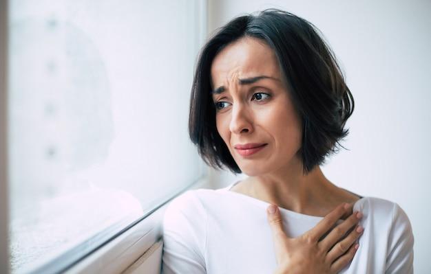 Doença séria. foto de close-up de uma jovem que está olhando pela janela e chorando, segurando a mão no peito.