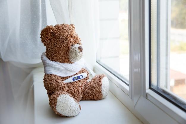 Doenças da infância do urso de peluche do conceito no fundo branco. urso de pelúcia sentado sozinho na janela branca